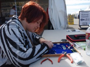 Lena Bugimenko demonstrating how to make a chainmaille bracelet