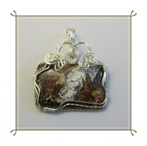 Joan Madouse wire wrapped this Mexican Crazy Lace agate in a rectangular frame with matching swirls of wire.