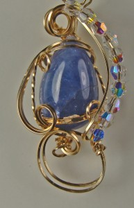 Gail Maas wire wrapped this opaque tanzanite cabochon with gold wire and crystal beads.