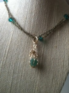 Emerald gem wrapped in gold filled wire