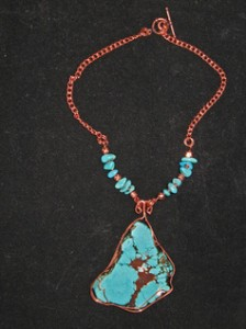 Linda Barton wrapped this turquoise magnesite stone in copper wire, and hung it on a necklace with copper and real turquoise beads.