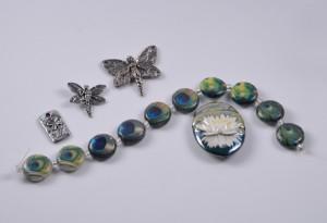 Green girl studio charms, peacock beads, and a lotus pendant