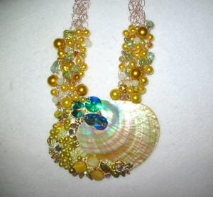 Diana Harwood used Swarovski Crystals and Crystal Clay to embellish this shell, which is on a crocheted wire necklace.