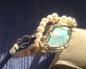 Jane Duke wire wrapped this larimar cabochon, forming a wire bracelet adorned with pearls